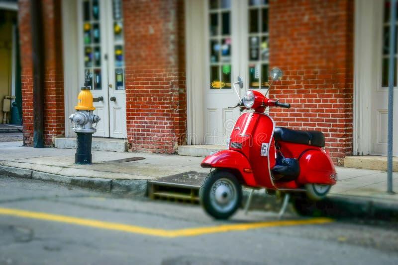 Gammalmodig röd sparkcykel på gatorna av den franska fjärdedelen i New Orleans royaltyfria foton