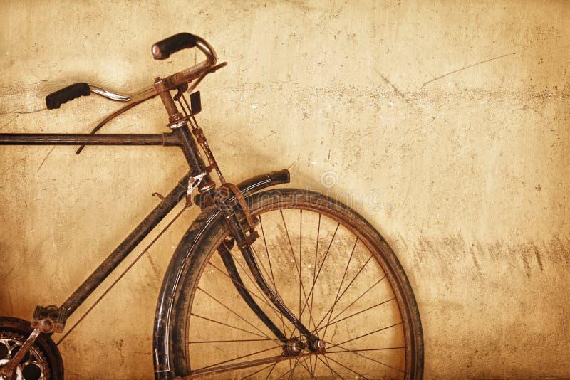 Gammalmodig rostig cykel nära väggen royaltyfri foto