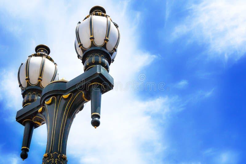 Gammalmodiga svarta och guld- streetlamps mot blå himmel fotografering för bildbyråer