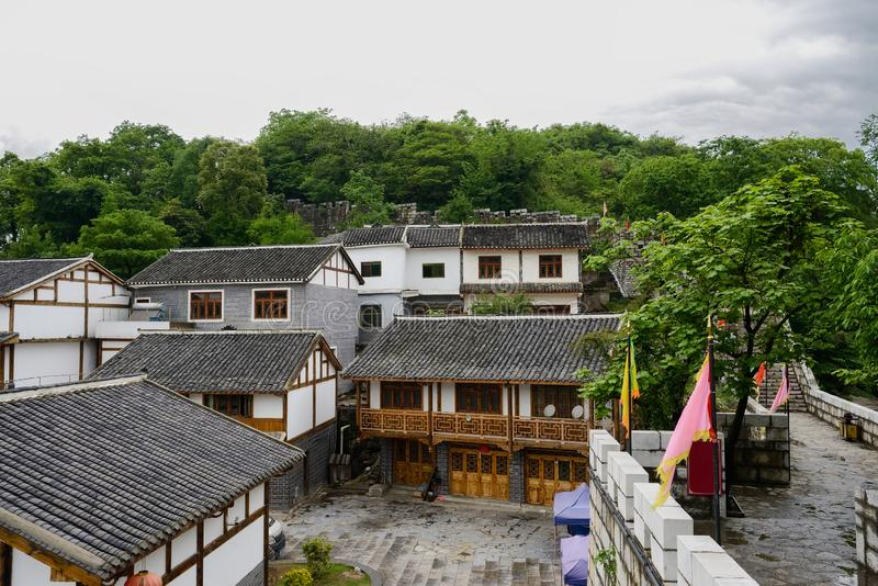 Gammalmodiga tegelplatta-taklade hus utanför stenväggen i molnig sp arkivbild