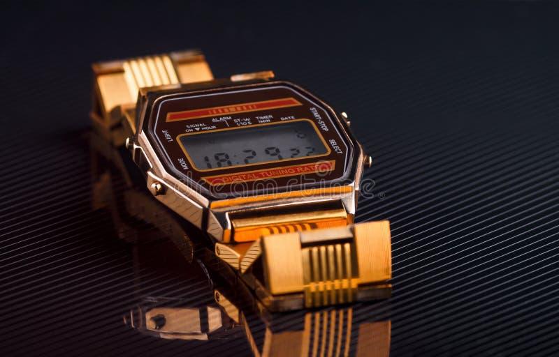 Gammalmodigt elektroniskt armbandsur på svart bakgrund tonat royaltyfri fotografi