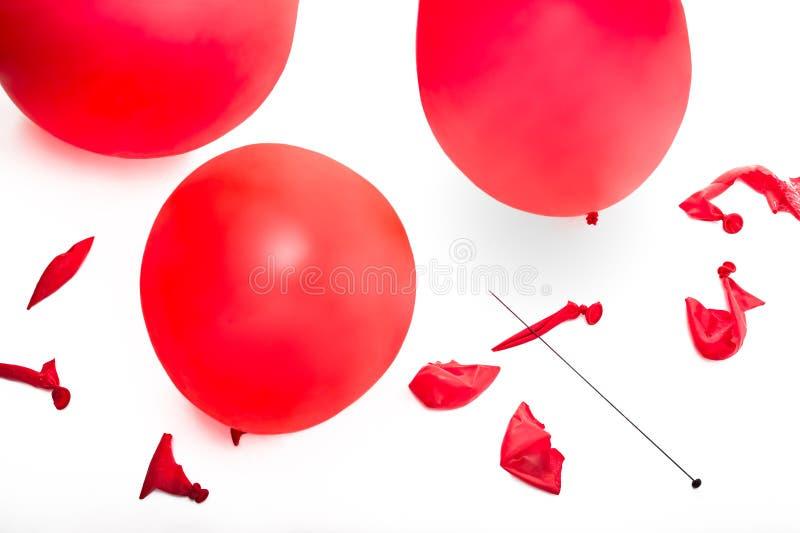Gammalmodigt hattstift och en samling av poppade och uppblåsta röda ballonger fotografering för bildbyråer