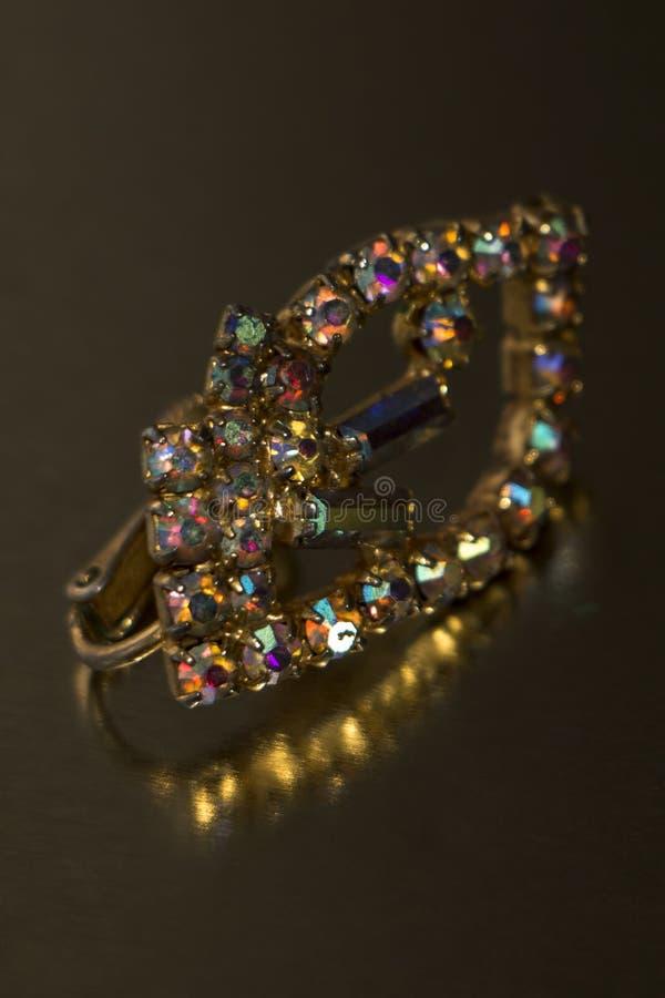Gammalt örhänge med ljusa mång--färgade stenar royaltyfri foto
