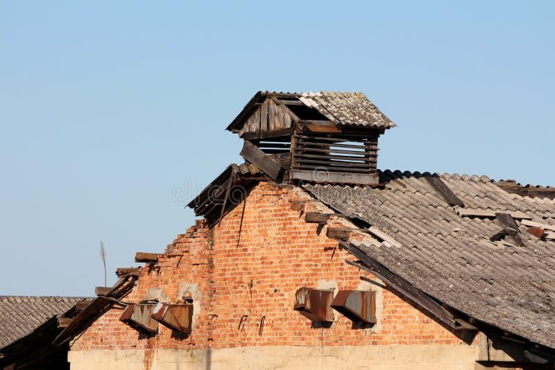 Gammalt övergett industriellt rostat lagringslager för röd tegelsten med det förstörda trätaket och vädra avgasrörfans arkivfoton
