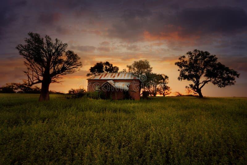 Gammalt övergett lantgårdhus för solnedgång royaltyfria bilder