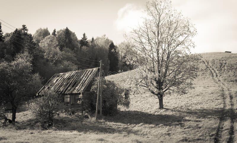 Gammalt övergett lantgårdhus under kullen fotografering för bildbyråer