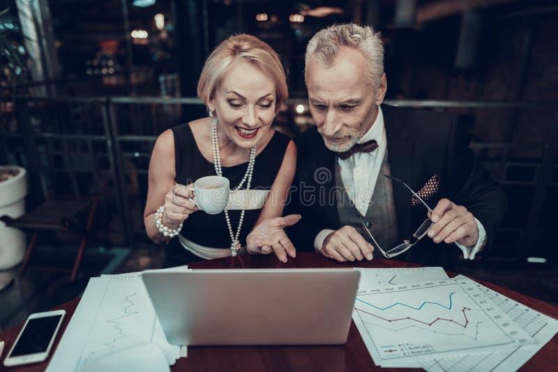 Gammalt affärsfolk som ser, i bärbar dator och att le arkivbilder
