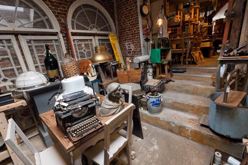 Gammalt antikt lager med många tappningredskap, dekor, trämöblemang, retro skrivmaskin och många detaljer arkivbild