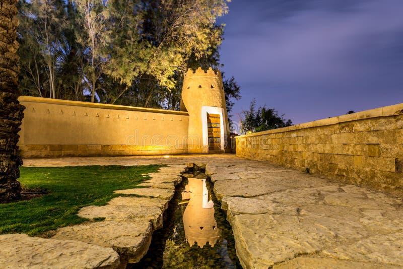 Gammalt arabiskt hus med dörren och trädgården - traditionell arabisk gyttjaarkitektur - del av en gammal saudier av sand för † royaltyfri foto