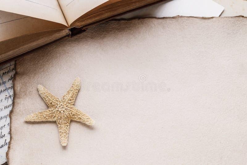 Gammalt ark av papper, böcker, bokstäver och en sjöstjärna royaltyfri fotografi