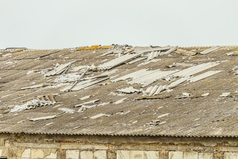 Gammalt asbest-cement tak av en förfallen jordbruks- byggnad arkivbild