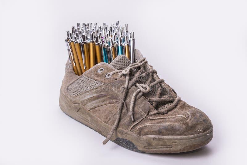 Gammalt bär ut skomaterielet med lotten av pennor royaltyfri foto