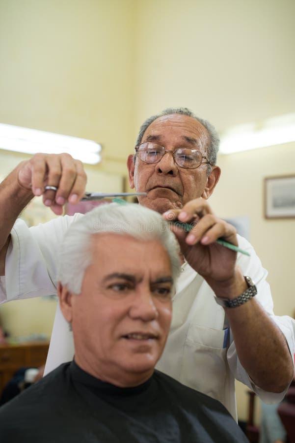Gammalt barberarecuttinghår till beställaren i barberare shoppar arkivbild