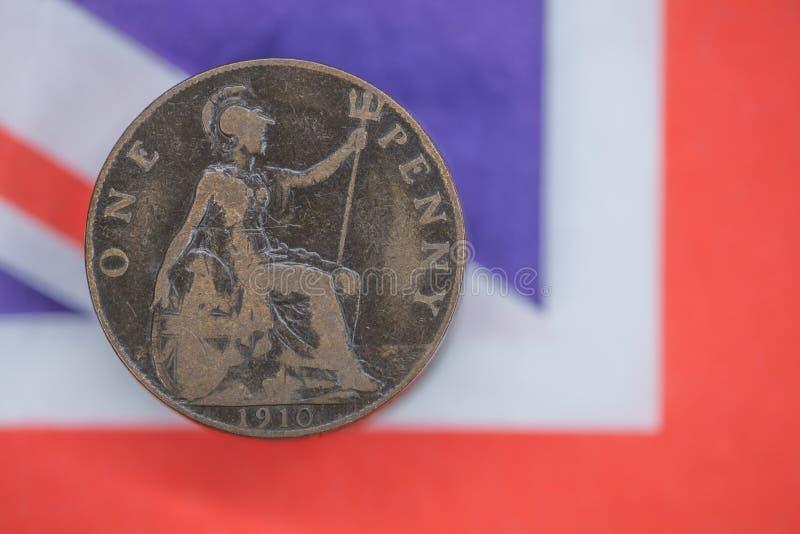 Gammalt brittiskt penny-mynt med unionsflagga utan fokus mot bakgrund royaltyfri foto