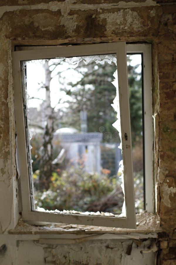 Gammalt brutet fönster med en sikt till yttersidan royaltyfri fotografi