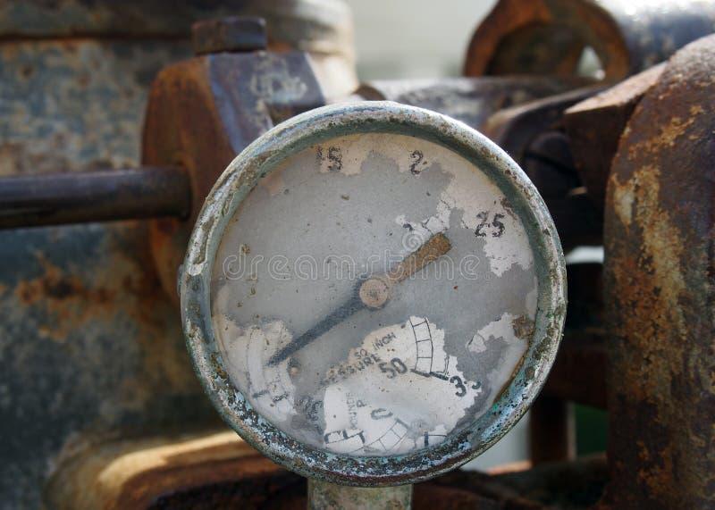 Gammalt brutet mått med spår av nummer på visartavlan på en stor gammal rostig motor royaltyfria foton