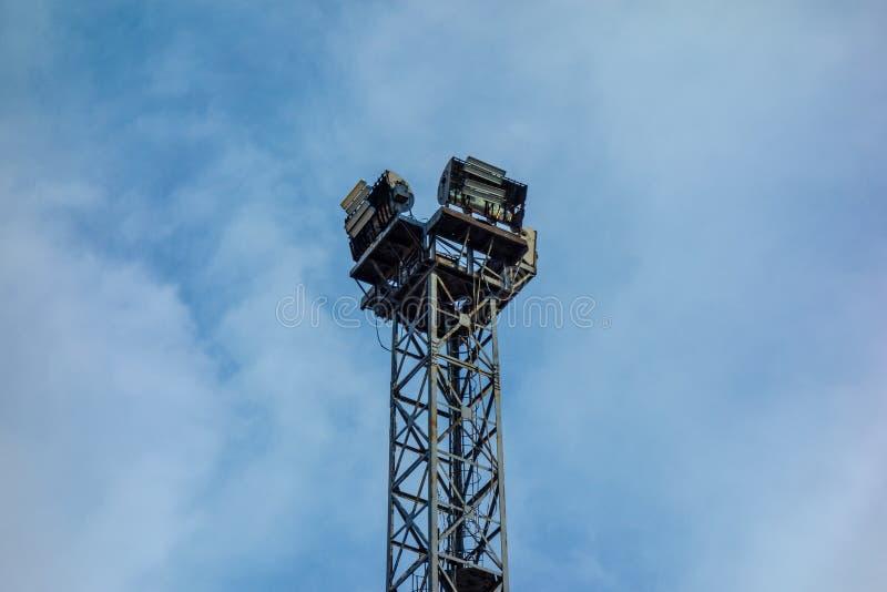 Gammalt enormt industriellt system för fläckljuslampa på bakgrund för blå himmel Åldrig konstruktion för metalltornram med krafti royaltyfri foto