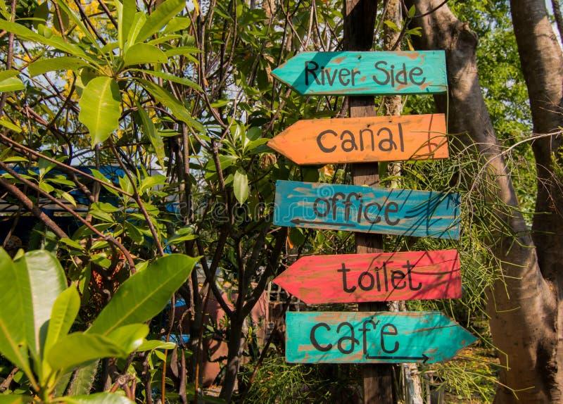 Gammalt färgrikt trätecken som pekar vägen, flodsida, kanal, kontor, toalett, kafé royaltyfri foto