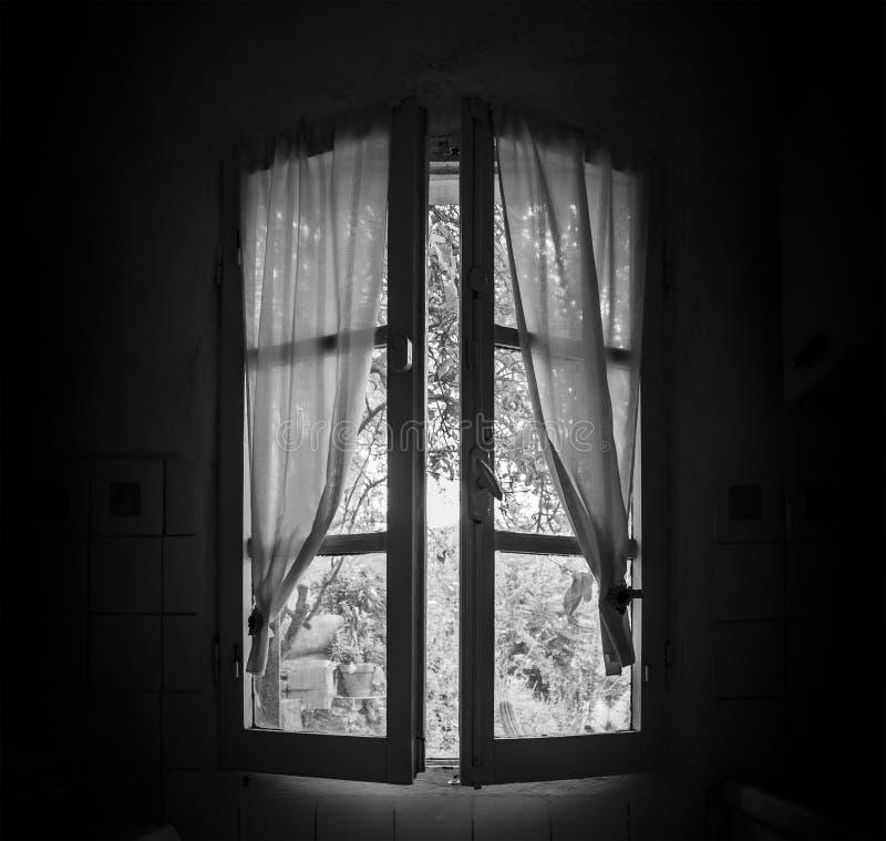 Gammalt fönster i ett mörkt rum royaltyfri bild