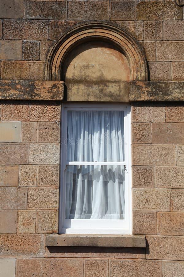 Gammalt fönster med med den vita ramen och gardiner arkivbilder