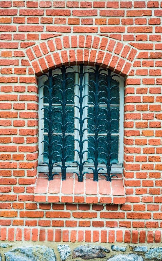 Gammalt fönster med galler- och tegelstenstenar royaltyfri bild