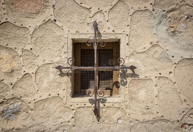 Gammalt fönster med metalliska skyddsstänger på en forntida vägg arkivfoton