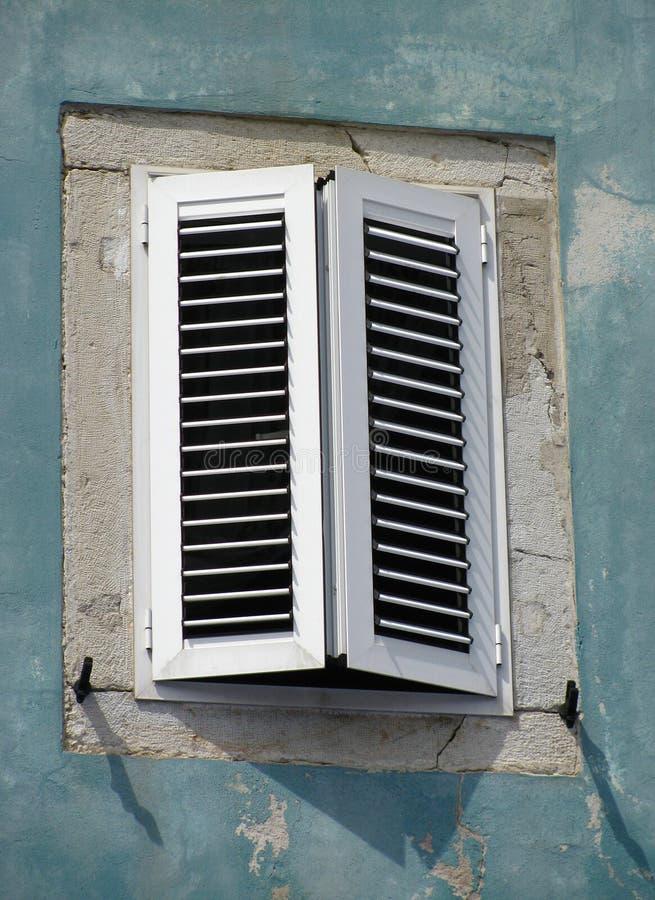 Gammalt fönster på den gröna väggen arkivfoton