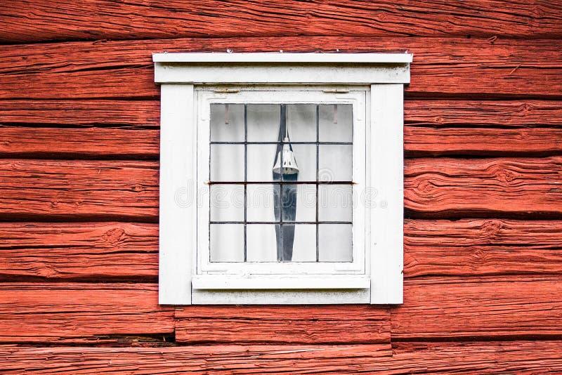 Gammalt fönster på rött träbråtehus royaltyfri bild