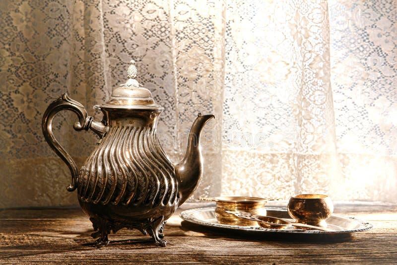 Gammalt försilvra teapoten och magasinet för Teaportiontillbehör royaltyfri bild