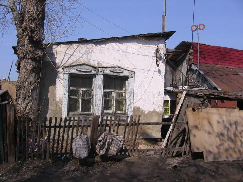 Gammalt förstört hus i den Siberian byn av oreglerat med vit murbruk fotografering för bildbyråer