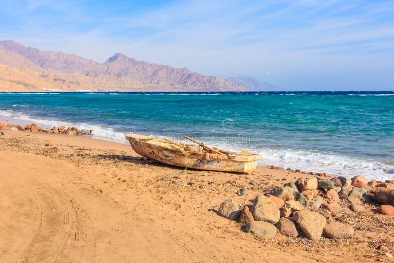 Gammalt fartyg på kusten, berg i bakgrunden arkivbild