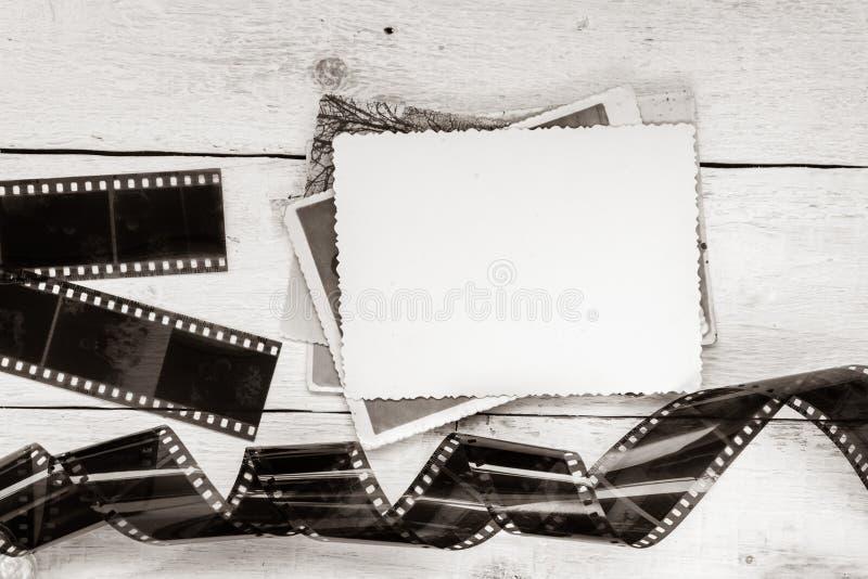 Gammalt film och foto på vit träbakgrund Tom ram för design arkivbild
