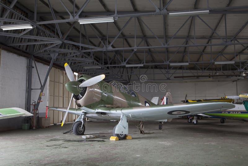 Gammalt flygplan i en hangar arkivbilder