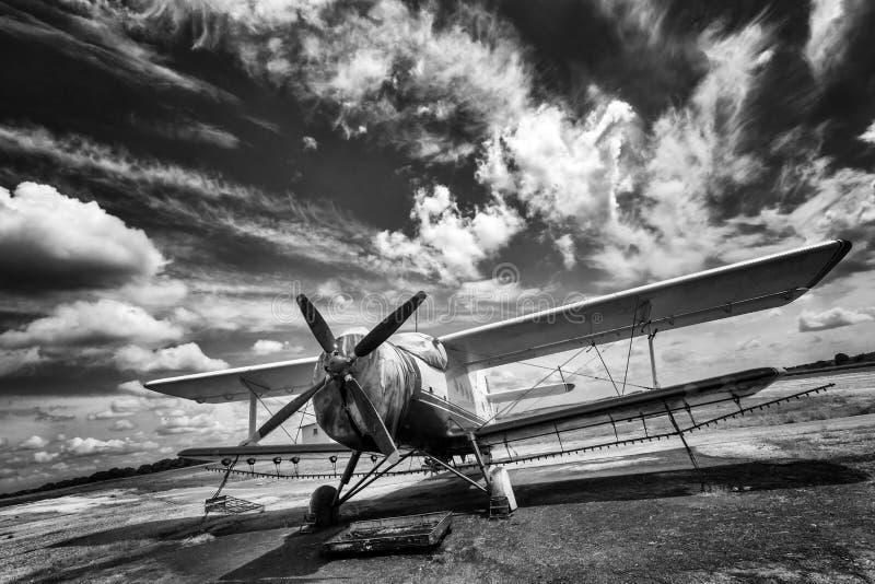 Gammalt flygplan på fält svart white royaltyfria bilder