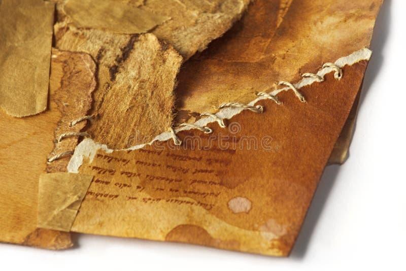 Gammalt forntida pappers- sönderrivet i stycken som tillbaka tillsammans kommas med igen, sy arkivfoton