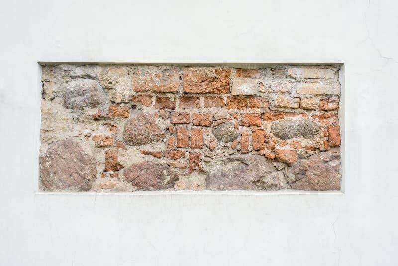 Gammalt fragment för stenvägg i vit rappad vägg som bakgrundsram royaltyfria bilder