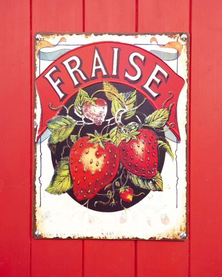 Gammalt Fraise Enamel tecken på en röd träbakgrund royaltyfria bilder