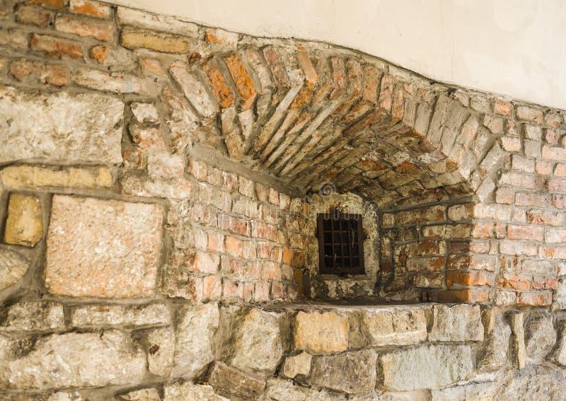 Gammalt gallerförsett fönster i ett medeltida fästningfängelse för gammal sten i Lviv Ukraina royaltyfri bild