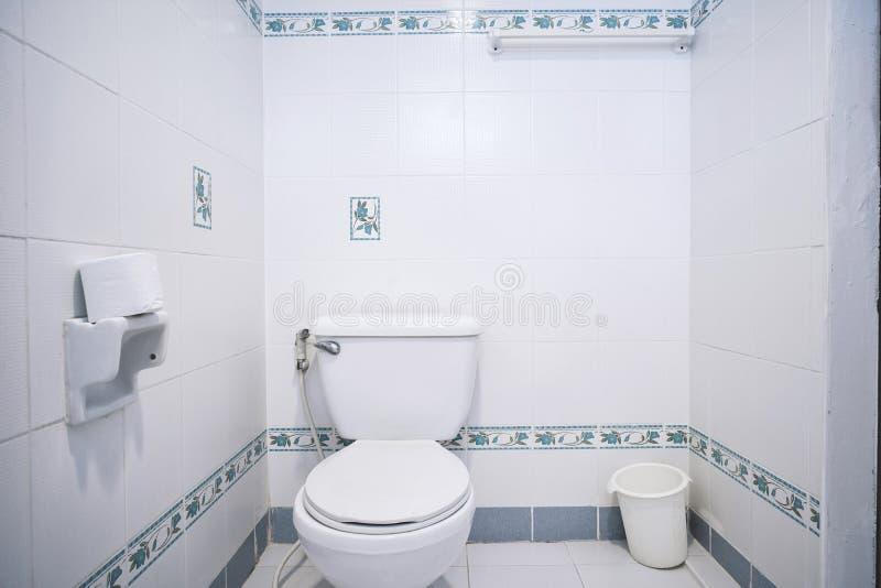 Gammalt generiskt toalettrum av lägenheten eller slät toalett för litet hotell med den enkla tegelplattamodellen arkivfoton