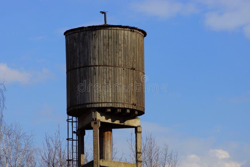 Gammalt grått trävattentorn mot en blå himmel och moln royaltyfri bild