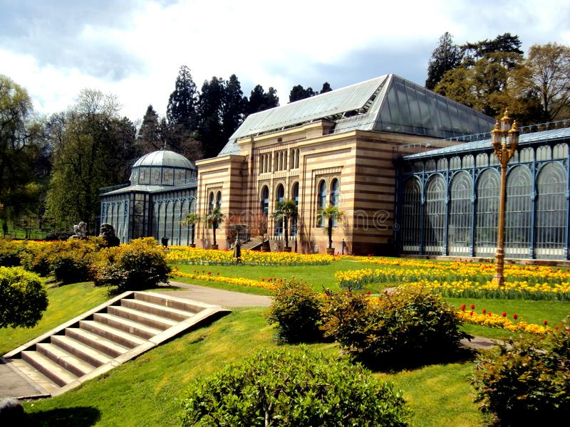 Gammalt grönt hus i härlig formell trädgård parkera offentligt med vårblommor i Stuttgart, Tyskland, Europa royaltyfria foton