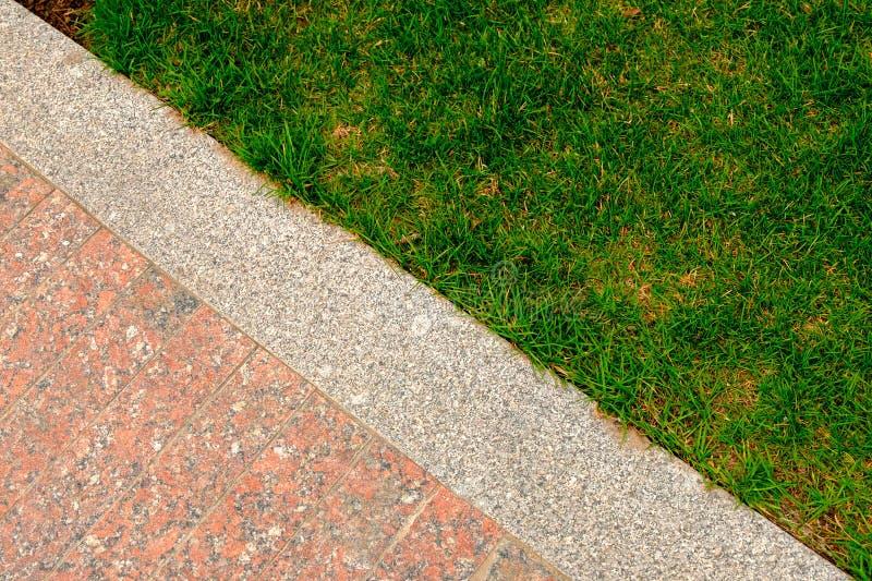 Gammalt granittrottoar och gräs i trädgårds- dekorativ textur, linje som delar naturen och civilisation, begrepp royaltyfria bilder