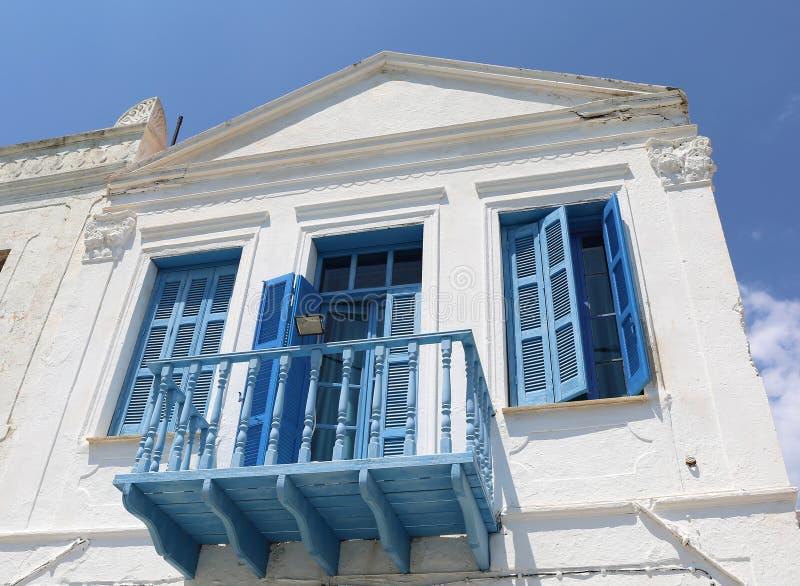 Gammalt grekiskt hus med den blåa fönsterslutare, balkongen och dörren royaltyfri bild