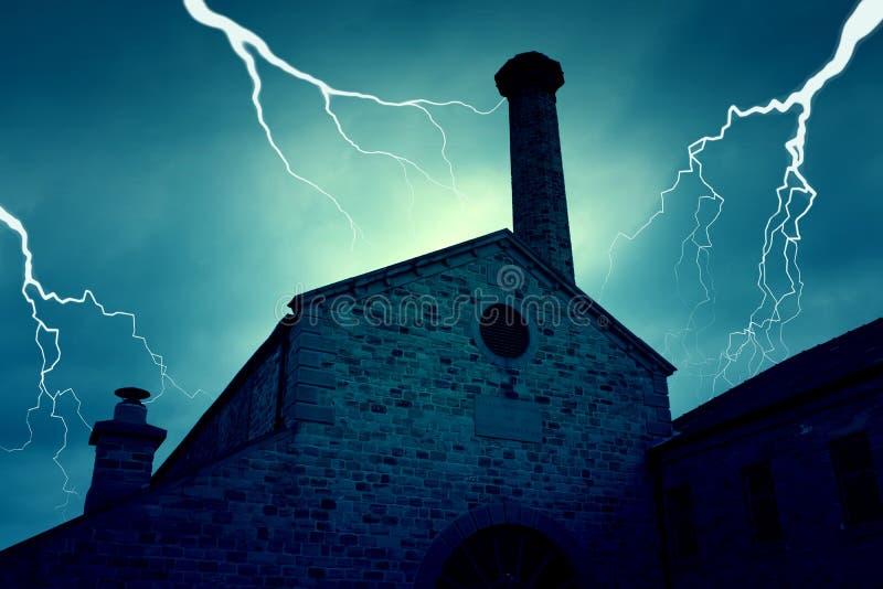 Gammalt herrelöst gods övergiven spökad byggnad med blixt arkivbild