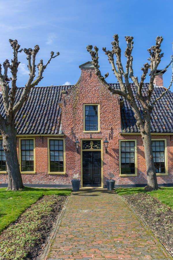 Gammalt hus för röd tegelsten i den hisorical byn av Aduard arkivbilder