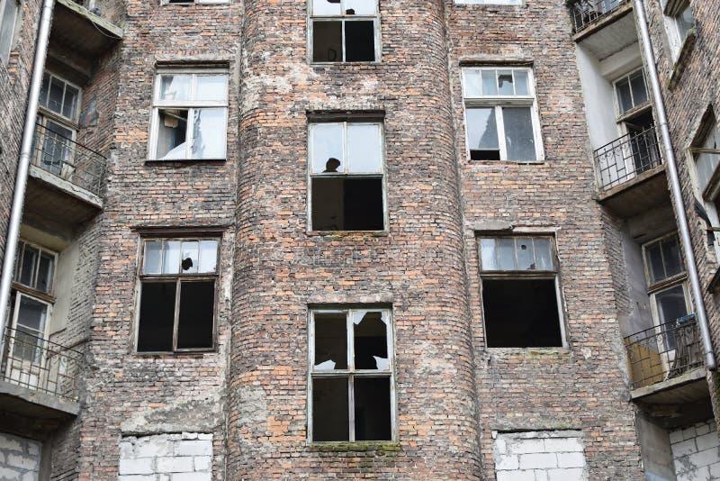 Gammalt hus för röd tegelsten med brutna fönster, tidigare judisk getto i Warszawa arkivfoto