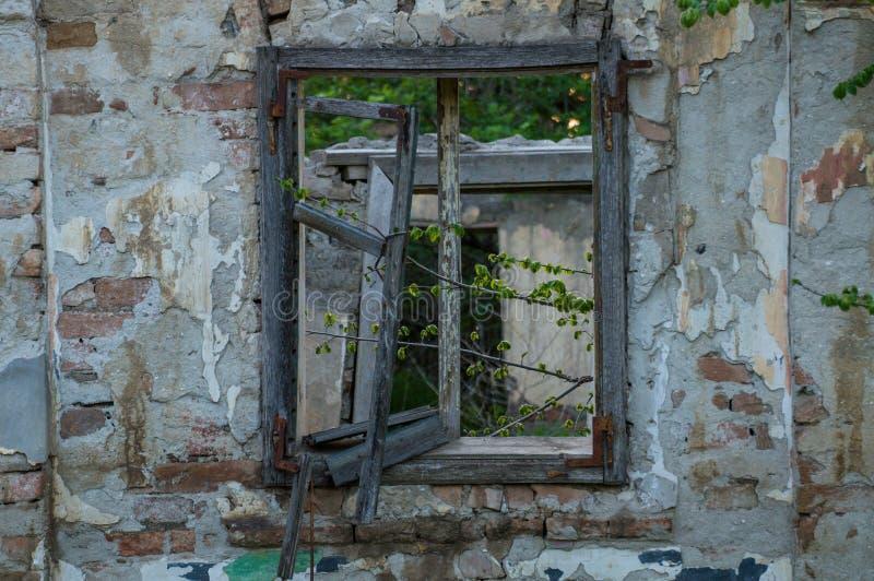 Gammalt hus i en by med ett brutet träfönster kopiera avst?nd arkivbild