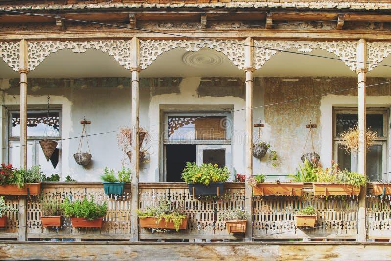 Gammalt hus i Tbilisi, Georgia med den härliga terrassen Gammal forntida traditionell träbalkong som dekoreras med lotten av blom royaltyfri bild