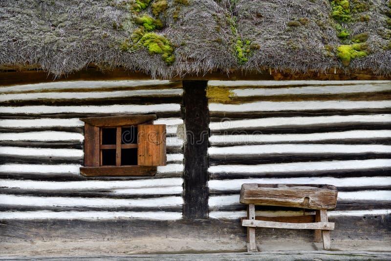 Gammalt hus med det lilla träfönstret och bänk i en romani tappning arkivbilder