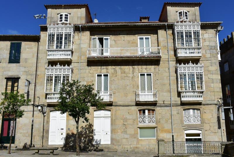 Gammalt hus med vita järngallerier i en fyrkant Vita fönster och ledstänger Pontevedra gammal stad, Galicia, Spanien, solig dag royaltyfria foton